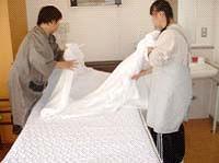 ろうじんホームでジョブコーチといっしょにベッドのシーツをかえています